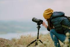 Fucilazione della giovane donna con la macchina fotografica alla mattina Treppiede e macchina fotografica mirrorless fotografia stock libera da diritti