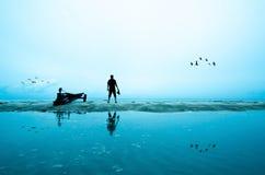 Fucilazione della siluetta del fotografo vicino alla spiaggia Fotografia Stock