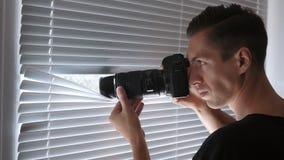 fucilazione della spia 4K, dei paparazzi o dell'agente investigativo sulla macchina fotografica attraverso i ciechi di finestra archivi video