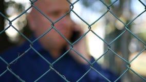 Fucilazione vaga con l'uomo che parla con cellulare dietro di un recinto metallico video d archivio