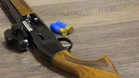 Fucile da caccia con le pallottole su fondo di legno immagine stock libera da diritti