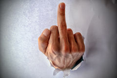 Fuck you - sign on the male hand from a hole in the paper. The middle finger sign. Stock Photography
