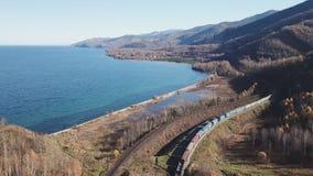 Fuco aereo di giorno di inverno seguire il treno turistico dei passeggeri ferroviari transsiberiani vicino al lago Baikal Profess archivi video