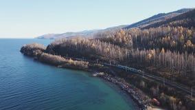 Fuco aereo di giorno di inverno seguire il treno turistico dei passeggeri ferroviari transsiberiani vicino al lago Baikal Profess stock footage