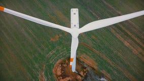 Fuco che pilota molto vicino fino alla turbina funzionante con le bande rosse, concetto ecologico alternativo del mulino a vento  stock footage