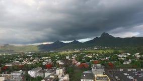 Fuco che sorvola la città di Belle Etoile in Mauritius, vicino a Port Louis Cielo e montagna tempestosi nel fondo stock footage