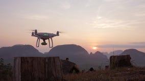 Fuco di Quadcopter che decolla nel parco alla bella alba con le montagne su fondo Phang Nga, Tailandia stock footage