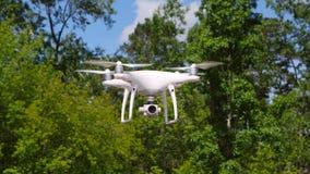 Fuco di Quadrocopter con la macchina fotografica Fuco moderno di RC Volo dell'elicottero contro il fondo vago verde Fotografia Stock