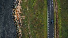 Fuco di vista superiore che segue automobile nera che si muove lungo la strada della baia di autunno molto vicina alla bella riva archivi video