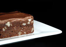 Fudge Brownie with Chocolate Icing. A moist, fudge chocolate brownie with nuts and chocolate icing on a square white plate on a black background Royalty Free Stock Image