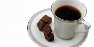 Fudge And Coffee Indulgences. A steaming cup of hot coffee in a pretty cup and several chunks of chocolate fudge make for a decadent afternoon snack. Over a stock images