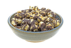 Fudge drizzled popcorn in an old bowl. A serving of fudge drizzled popcorn in an old stoneware bowl isolated on a white background Royalty Free Stock Photography