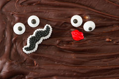 Fudge for two. Funny faces representing of a man with a mustache and a female with red lips in home made chocolate fudge Royalty Free Stock Photography