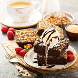 Fudgy brownies with nuts and caramel. Fudgy brownies with nuts, chocolate and caramel syrup and a scoop of ice cream Stock Photo