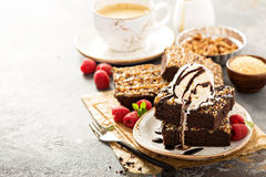Fudgy brownies with nuts and caramel. Fudgy brownies with nuts, chocolate and caramel syrup and a scoop of ice cream Royalty Free Stock Image
