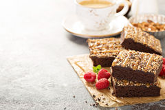 Fudgy brownies with nuts and caramel. Syrup and a cup of coffee Royalty Free Stock Photo