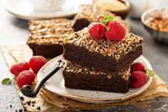Fudgy brownies with nuts and caramel. Syrup and a cup of coffee Stock Images