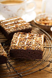 Fudgy brownies with nuts and caramel. Syrup and a cup of coffee Royalty Free Stock Image