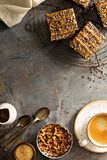 Fudgy brownies with nuts and caramel. Syrup and a cup of coffee overhead shot Stock Image