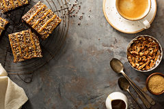 Fudgy brownies with nuts and caramel. Syrup and a cup of coffee overhead shot Royalty Free Stock Photo