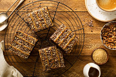 Fudgy brownies with nuts and caramel. Syrup and a cup of coffee on wooden table overhead shot Stock Photos