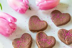 Fudgy Rum Valentine`s Candies. Chocolate heart candies lightly flavored with a touch of rum extract, decorated with sprinkles and pink tulips stock images