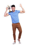 Fudll body picture of a man winning trophy cup. Fudll body picture of a man winning a trophy cup and holding it on his shoulder Stock Photo