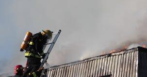 Fuego ardiente de la casa Agua del espray de los bomberos en el tejado con la manguera almacen de video