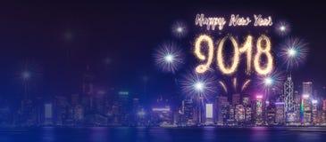 Fuego artificial 2018 de la Feliz Año Nuevo sobre el paisaje urbano que construye cerca del mar en Foto de archivo libre de regalías