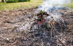 Fuego bajo al aire libre con humo y ascuas imagen de archivo libre de regalías