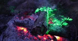 Fuego brillante y ferviente en la noche con una luz laser verde metrajes