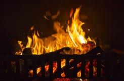 Fuego caliente ardiente en un lugar del fuego con los registros y los carbones de madera fotos de archivo