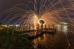 Fuego de las lanas de acero en la orilla del lago imagen de archivo