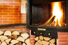 Fuego de madera caliente que quema en un parte movible de la chimenea Imagen de archivo