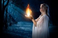 Fuego de tenencia de la muchacha de Elven en palmas en el bosque de la noche Imágenes de archivo libres de regalías