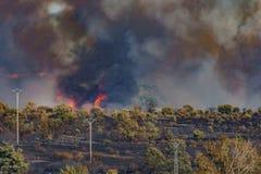 Fuego en el desierto con las torres eléctricas Foto de archivo libre de regalías