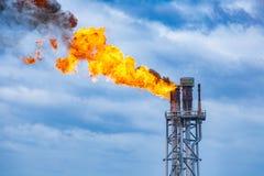 Fuego en pila de llamarada en la plataforma de proceso central del petróleo y gas mientras que quema el tóxico y el lanzamiento s fotografía de archivo