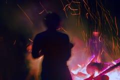 Fuego enorme en la noche y la gente joven alrededor Foto de archivo