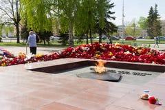 Fuego eterno contra día de las flores después del 9 de mayo de la gran victoria, celebración de la victoria en la Segunda Guerra  Fotografía de archivo