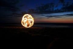 Fuego poi en la playa en puesta del sol Imagen de archivo