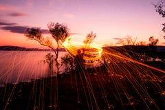Fuego Poi en la puesta del sol en el lago Foto de archivo