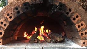Fuego que quema en el combustible en chimenea anaranjada vieja del ladrillo almacen de metraje de vídeo