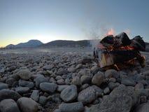 Fuego que se calienta en la orilla fría congelada del río Blanco Imagenes de archivo