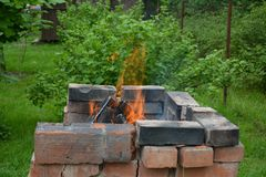 Fuego sobre la madera en el hogar en el jardín fotos de archivo libres de regalías