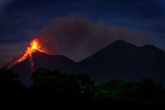 Fuego volcano erupting in Guatemala just before dawn. Lava & smoke spurt from erupting Fuego volcano next to Acatenango volcano at dawn near Antigua, Guatemala royalty free stock photos
