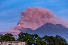 Fuego volcano erupting in Guatemala. Lava & smoke spurt from erupting Fuego volcano next to Acatenango volcano at dawn near Antigua, Guatemala, Central America royalty free stock images