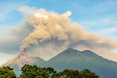 Fuego volcano erupting in Guatemala. Smoke spurts from erupting Fuego volcano next to Acatenango volcano just after dawn near Antigua, Guatemala, Central America stock photography