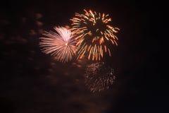 Fuegos artificiales anaranjados y amarillos en el cielo oscuro Imagen de archivo