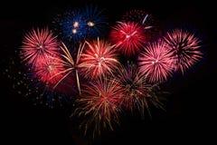 Fuegos artificiales azules de oro rojos sobre el cielo nocturno Imagen de archivo
