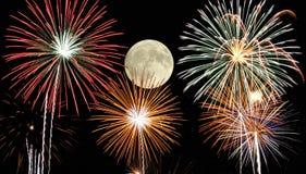 Fuegos artificiales bajo claro de luna imagen de archivo